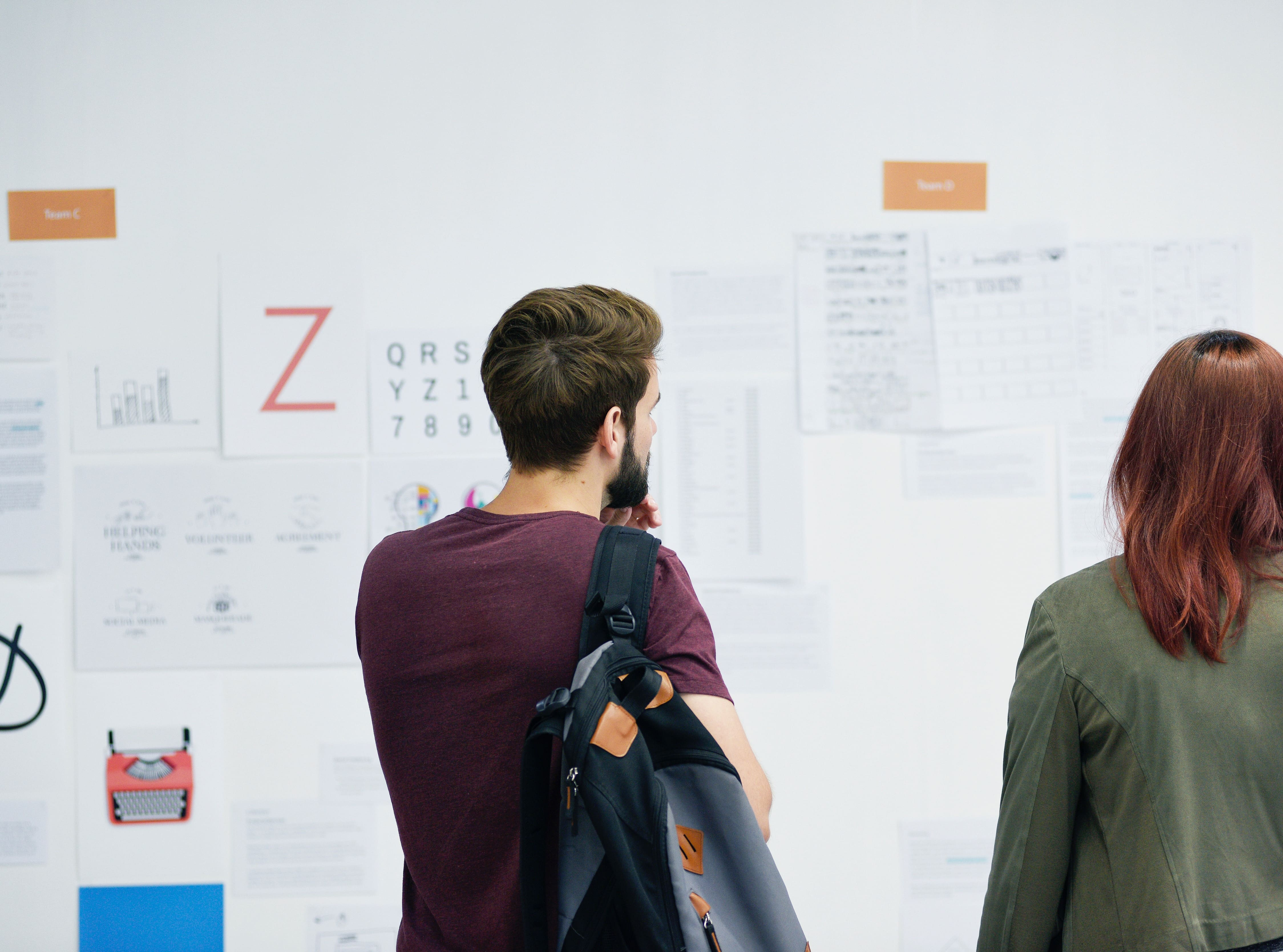 Hombre y mujer joven leyendo noticias en tablón de anuncios